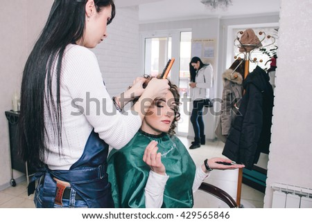 Dneprodzerzhinsk, Ukraine - March 28, 2016: Hairdresser makes fashion wedding hairstyle for young beautiful bride