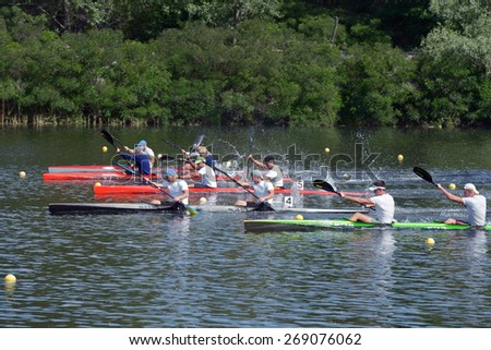 DNEPROPETROVSK, UKRAINE - MAY 29, 2013: Kayak racing during Ukrainian paddling championships. Dnepropetrovsk rowing canal is the main Ukrainian sport arena in kayaking and canoe racing - stock photo