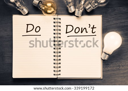 Do and Don't sorting table on notebook with light bulbs - stock photo