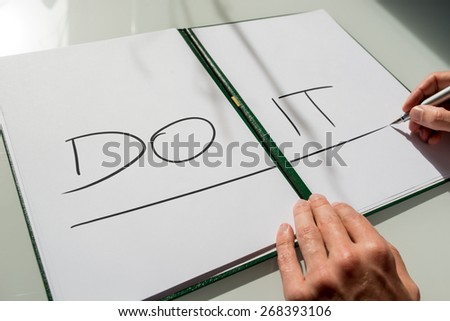Do It concept with the hand of a man writing the words in large capital letters across an open notebook conceptual of - do not procrastinate, do it immediately. - stock photo