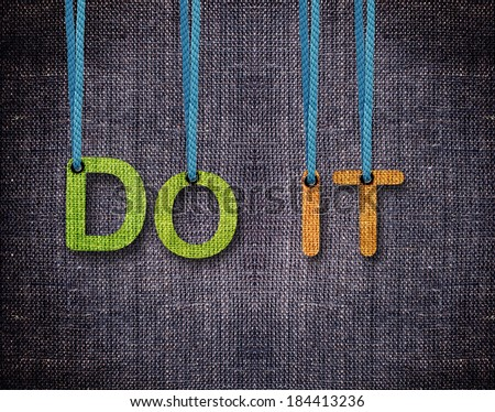 Do it Letters hanging strings with blue sackcloth background. - stock photo