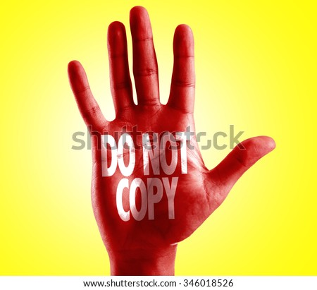 Do Not Copy written on hand with yellow background - stock photo