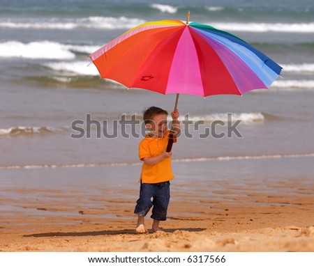 Do not depend on weather conditions. Cute small boy with big brightly colored umbrella having fun on the beach - stock photo