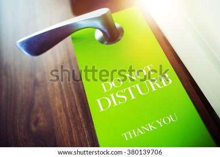 Do Not Disturb Green Paper Hotel Door Hanger. Pleasure Stay in Hotel Concept. Travel Concept. - stock photo