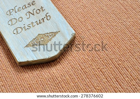 Do not disturb wooden sign with space on the fabric background - stock photo