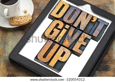 do not give up - motivation concept - a phrase in vintage letterpress wood type printing blocks on a digital tablet with a cup of coffee - stock photo