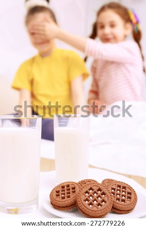 Do not look. Two little nice girls standing behind cookies and milk and hugging. - stock photo