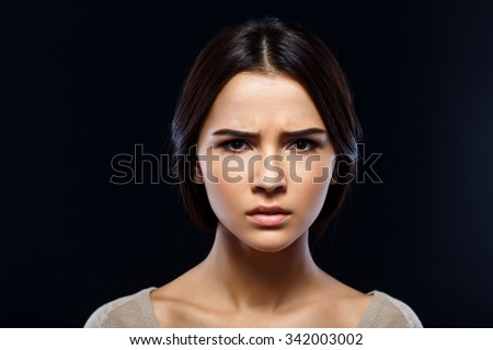 Do not puzzle me. Close up of upset disappointed young woman feeling  sullen while standing isolated on black background - stock photo