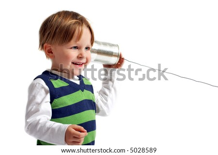 Do you hear me? Very cute 3-years old boy casual dressed playing with self-made phone. - stock photo