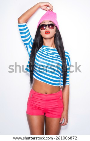 Do you like my hat? Playful young African woman in funky stretching her hat and looking up while standing against white background - stock photo