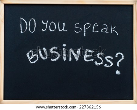 Do you speak business? message written with white chalk on wooden frame blackboard
