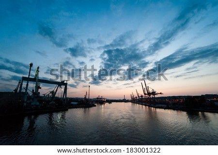 Dock cranes in cargo terminal with visible shapes of containers against dusk sky background, visible port entrance and harbor. - stock photo