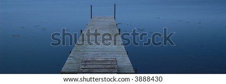 dock extending into a lake at dusk, long exposure - stock photo