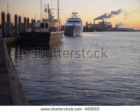 Dock, moored boats and industry against sunset - stock photo