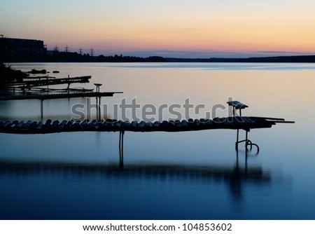 dock on the lake shore in the evening - stock photo