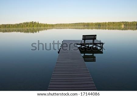 dock or pier on mirror calm lake in morning light - stock photo