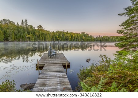 Dock with Adirondack Chairs at Sunset on a Lake in Ontario, Canada - stock photo