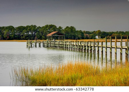 Dock with Boathouse leading out in the creek on a dark fall day - stock photo