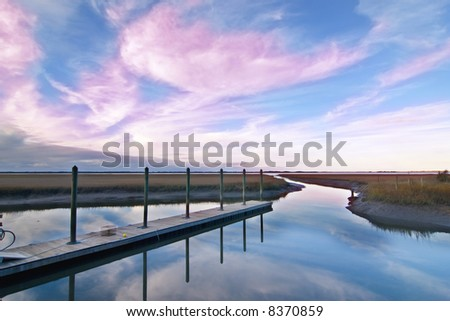 dock with crab trap at sunset on the south carolina coast - stock photo
