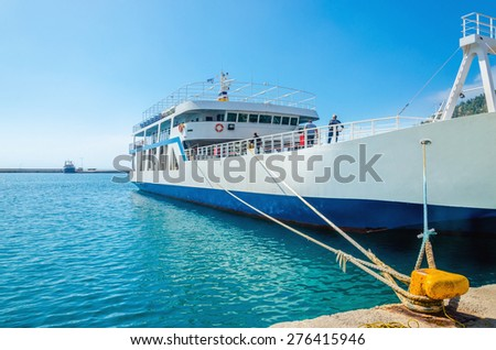 Docked Greek Ferry in painted typical blue-white colors waiting in harbour to be loaded with cars  - stock photo