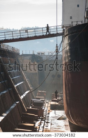 Dockers working in dry dock. - stock photo
