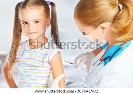 Doctor a pediatrician makes child vaccinated vaccination - stock photo