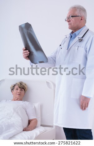 Doctor analyzing chest x-ray while patient lying in bed - stock photo