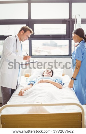 Doctor and a nurse stand around a patients bed as they are examining him in hospital - stock photo