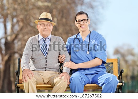 Doctor and an elderly gentleman sitting outdoors - stock photo