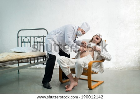Doctor and bizarre patient in a hospital - stock photo