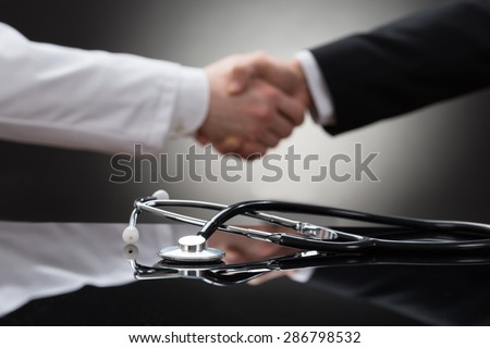 Doctor And Businessman Shaking Hand In Front Of Stethoscope - stock photo