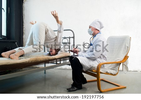 Doctor and crazy patient in a hospital - stock photo