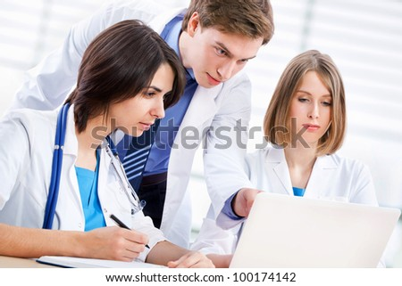 Doctor and his young collegues working at laptop - stock photo