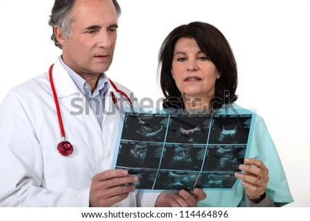 doctor and nurse examining a scanner image - stock photo