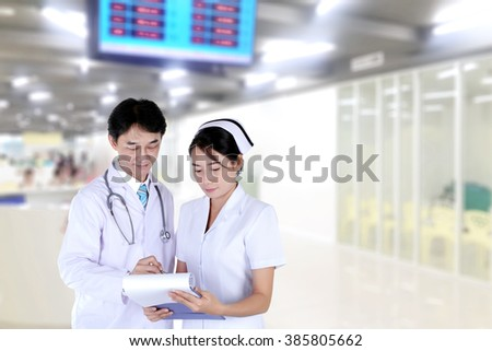 doctor and nurse reviewing medical chart,  in hospital hallway - stock photo