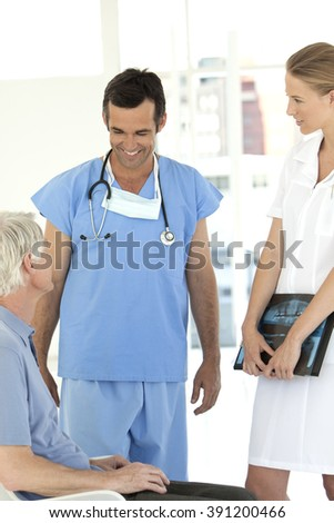 Doctor and nurse talking to senior male patient at the hospital