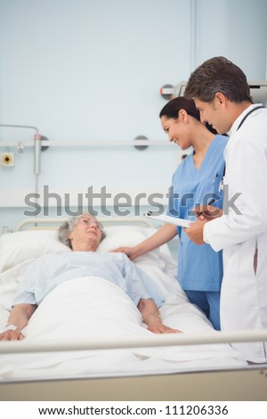 Doctor and nurse talking with a patient in hospital ward - stock photo