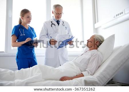 doctor and nurse visiting senior woman at hospital - stock photo