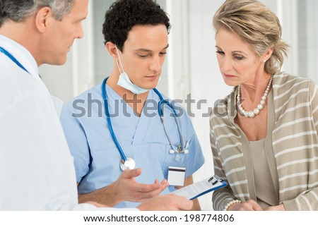 Doctor And Nurse With Medical Record Advising Female Patient In Hospital - stock photo