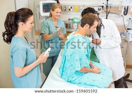 Doctor and nurses examining male patient in hospital room - stock photo
