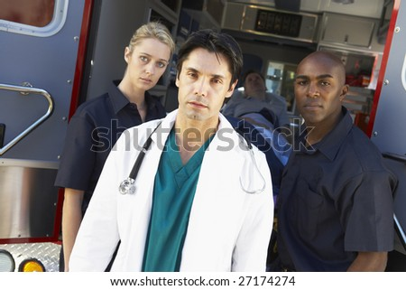 Doctor and paramedics standing in front of an ambulance - stock photo