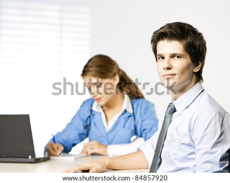 doctor and patient at doctors desk - stock photo