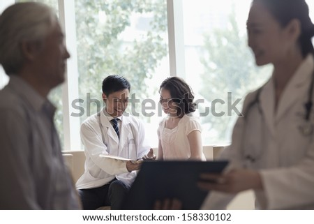 Doctor and patient sitting down and discussing medical record in hospital - stock photo