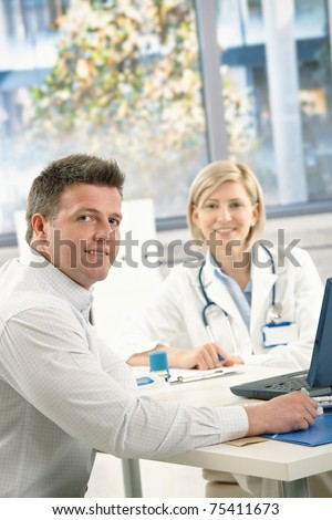 Doctor and patient sitting in office, looking at camera, smiling.?