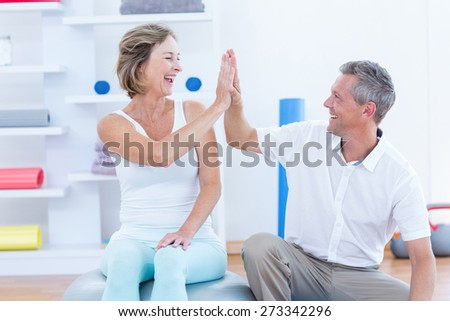 Doctor and patient smiling at each other in medical office - stock photo