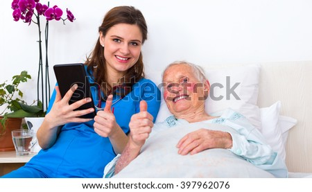 Doctor and senior patient showing thumbs-up at the nursing home, using digital tablet.