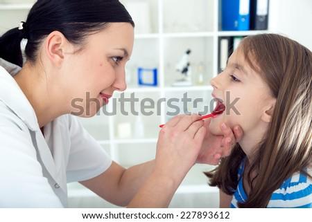 Doctor check throat of little girl. - stock photo