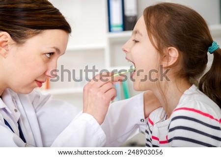 Doctor check throat of little girl - stock photo