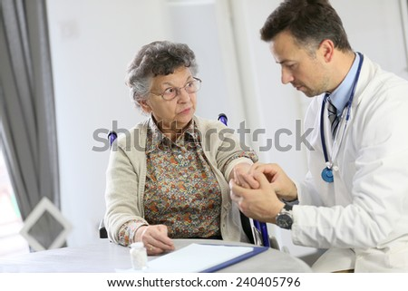 Doctor checking blood pressure to elderly woman