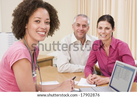 Doctor checking couples medical details - stock photo